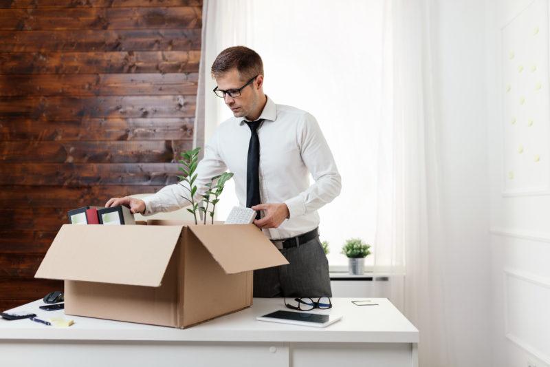 Mann packt sein Bürotisch zusammen