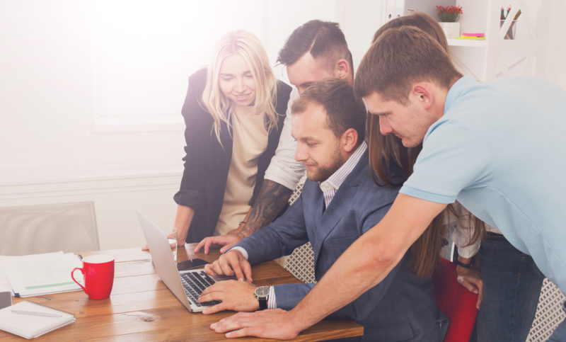 Happy business people team together look at laptop in office
