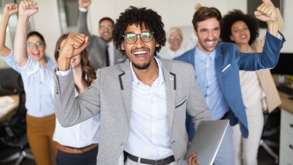 Glückliche Geschäftsleute feiern ihren Erfolg in einer modernen Firma