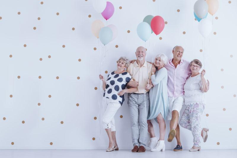 Glückliche Senioren mit Luftballons