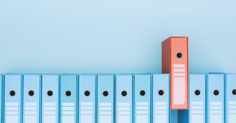 Eine Reihe mitn blauen Mappen und einer roten Mappe